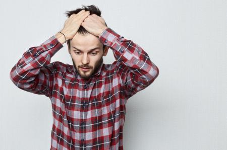 De jonge Kaukasische mens met baard in wanhoop behandelt zijn hoofd met handen. Zorgen vanwege problemen en stress. Gemiste kansen vanwege slecht geheugen. Menselijke emotie concept.