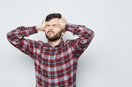 Studio shot van jonge verdrietige en depressieve man in shirt. Hij lijkt wanhopig in pijn, lijdt aan migraine en hoofdpijn, sluitende ogen. Geïsoleerd op een witte achtergrond. Negatief Emoties concept. Stockfoto