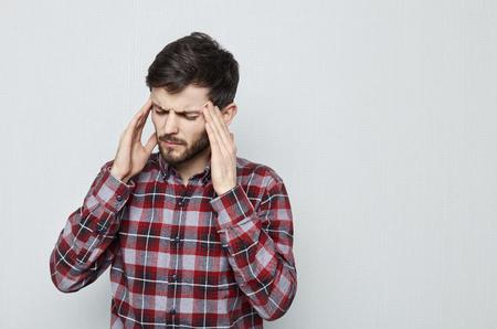 Portret van aantrekkelijke jonge man met baard dat haar hoofd lijdt aan pijn. Migraine en hoofdpijn. Overwerkte, stressvolle en zakelijke problemen.