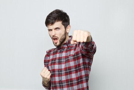 Studio shot van opgewonden jonge bebaarde man gekleed in casual shirt, demostrating zijn macht en superioriteit. Succes vieren met strakke vuisten en geopende mond kijken naar de camera. Stockfoto