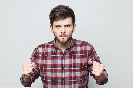 Studio close-up van blanke man die zijn vuisten in woede houdt en dreigt. Bebaarde hipster man in casual shirt kijkt uit Ã?â ? ° lendende jukbeenderen en klaar om te vechten. Menselijke emoties.