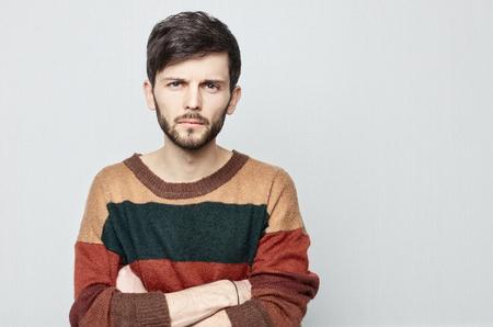Sudio shot van jonge brunette aantrekkelijke kerel staren naar de camera met verdenking. Blanke man in vintage trui kruist zijn handen en staren naar voren.