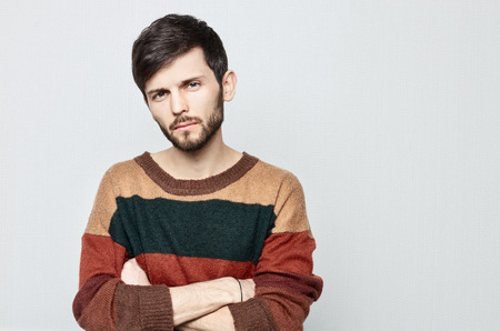 Studio portrait of young bearded hipster male looking upset, indifferent , shameful and Impolite. Dressed in oldfashioned colorful sweater guy crosses arms and stares in displeasure.