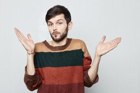 Studio shot van jonge bebaarde Causasian man in ouderwetse kleurrijke trui spreidt zijn handen in verbazing aan de zijkanten. Verrassend kijkt hij er naar uit. Menselijk emotioneel concept.
