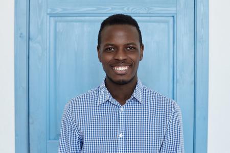 De knappe zekere jonge Afrikaanse Amerikaanse mens gekleed in toevallig blauw overhemd bekijkt camera met gelukkige glimlach, die zich tegen blauwe deur backgroung bevinden. Jeugd en geluk concept.