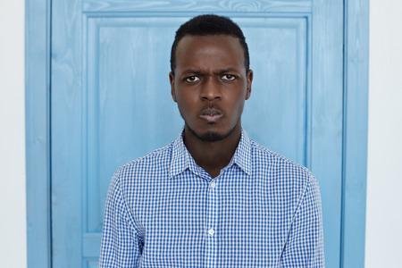 Sluit omhoog humeurig portret van de wantrouwende jonge mens die camera met sceptische verdachte uitdrukking, emotie bekijken. De jonge Amerikaanse het bureaumens van Afro is zorg over zijn salaris voor blauwe deur. Twijfel en verwarring concept.