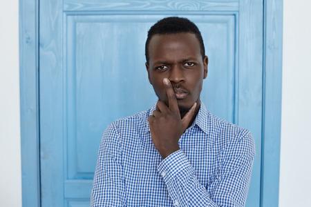 Op zoek naar een beslissing. Jonge talanted architectuur, ingenieur of zakenman zoekt het antwoord op de belangrijke vragen. Met een doordachte gezichtsuitdrukking kijkt hij ernaar uit om zijn kin met één hand vast te houden. Stockfoto