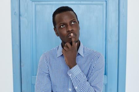 Portret van de jonge Afro-Amerikaanse man, hand op zijn kin, opkijkend met nadenkende en sceptische uitdrukking op zijn gezicht, vermoedend van iets, aarzelend om een ??beslissing te nemen. Studio die op blauwe deurachtergrond is ontsproten.