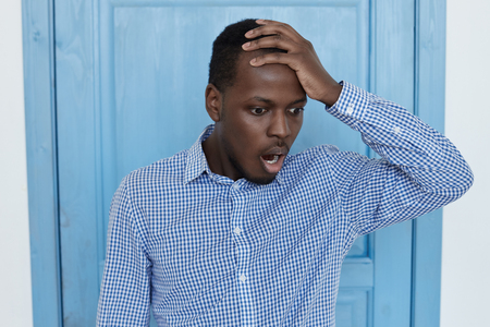 Studio shot van geschokte en wanhopige donkere man met een blauw shirt, met de hand op het hoofd, kijken naar beneden en schreeuwen met angst en mond open, vanwege een verschrikkelijke fout