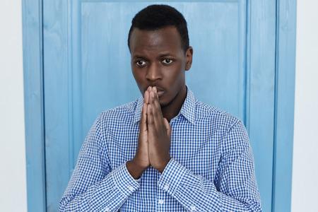 Biddende jonge Afro-Amerikaanse man in blauw shirt. handen samen drukken, boos van blik zijn, om vergeving vragen, hopen op betere tijden. Studio die bij blauwe deurachtergrond is ontsproten.