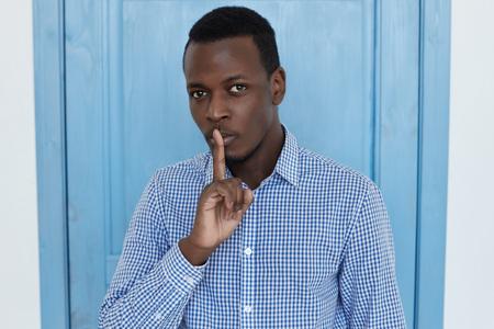 Close-upportret van de gesloten jonge knappe Afrikaanse Amerikaanse mens die vinger plaatsen op lippen die shh, stil, stilte vragen die, blauwe deurachtergrond vooruit eruit zien. Menselijke gezichtsuitdrukkingen, emotioneel concept. Stockfoto