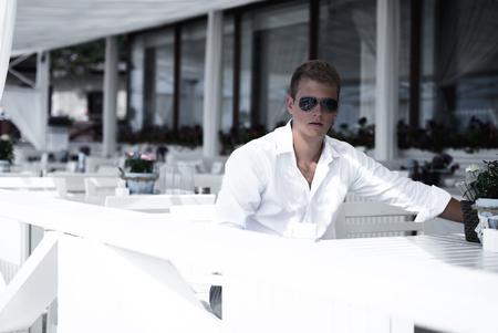 De jonge en ernstige model kijkende kerel zit bij kustrestaurant, dat meisjes van het strand gaat halen. Dapper kijken naar de camera door stijlvolle zonnebril. Jeugd en schoonheid concept. Stockfoto