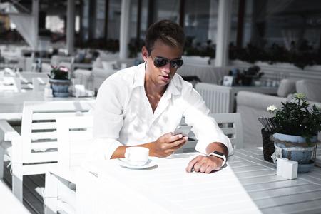 De jonge modieuze en modieuze mens met smartwatch op zijn hand controleert zijn telefoon en drinkt thee in openlucht koffiereep bij zonnige de zomerdag.