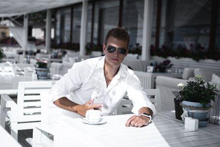 Jonge Kaukasische stijlvolle man in zonnebril is aan het drinken van koffie en gaat de oproep beantwoorden. Zittend alleen en kijken naar de camera in wit interieur open cafe een warme zonnige dag.