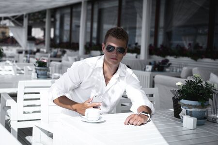 Young Caucasian stylish male in sunglasses is drinking coffee and going to answer the call. Sitting alone and looking at the camera in white interior open cafe one warm sunny day.