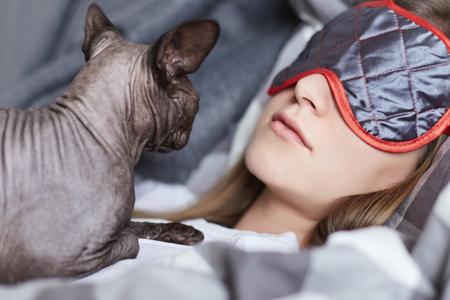 Zeer dicht omhoog geschoten van twee beste vrienden die dutje in een dag nemen. De oosterse kat ligt op een meisjesborst, draagt ??de jonge dame oog het slaapmasker hiddng van daglicht. Huisdieren en menselijk concept. Stockfoto