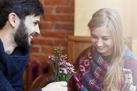 Gelukkige jonge lachende paar liefhebbers die in moderne coffeshop dateren. In de koude tijd van het seizoen mooi koppel draagt warme kleding. De man geeft zijn vrouw een freaker. Jong en geluk concept. Stockfoto