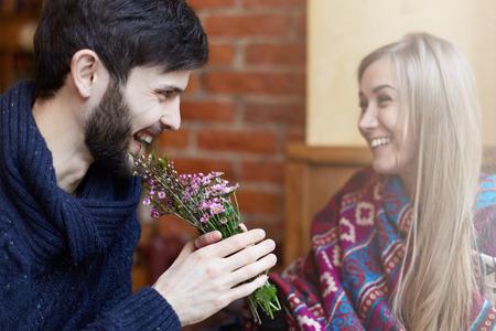 Focus op de man die bloemen uit een jonge aantrekkelijke dame neemt. Een paar liefhebbers lachen in een gezellig café, met goede tijd en genieten van elkaar.