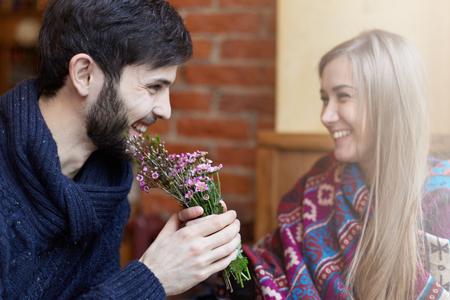 Hand aan hand jonge gelukkige paar met verse bloemen genieten van zoete tijd samen. Twee jonge vrolijke mensen op een date die comfortabele, warme kleding dragen. Stockfoto