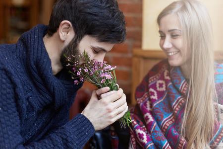 Focus op jonge knappe blanke man die ruikt verse bloemen op een datum met lachende jonge mooie dame. Het dragen van casual warme kleding brengt de gelukkige tijd samen door in een moderne coffeeshop.