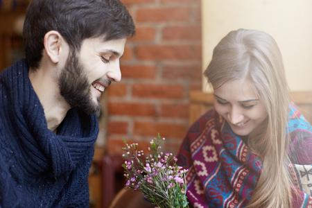 Een paar jonge blanke mannen en vrouwen hebben goede tijd in een moderne koffiekop, praten en lachen gelukkig. Het dragen van warme, trendy kleding op een koude maar zonnige dag.