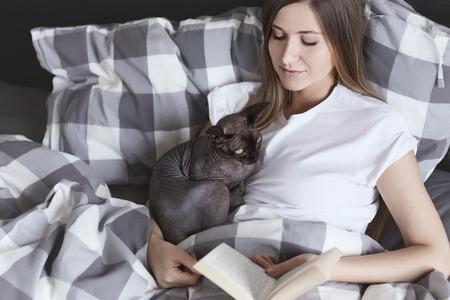Jonge mooie vrouw die in bed tot aan de middag blijft, niets doet, leesboek met haar dwaze sfinxkat. Lazy aantrekkelijk meisje met een gezonde huid in natuurlijke rommelige beddengoed achtergrond.