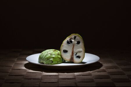 rimmed: Sliced Cherimoya on gold rimmed white plate in the spotlight