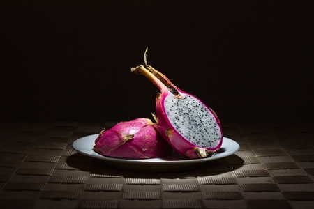 rimmed: Sliced Dragon Fruit on gold rimmed white plate in the spotlight