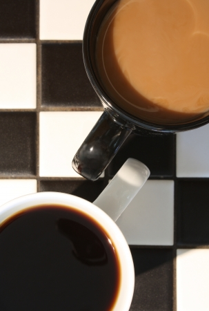 Two cups of coffee, one white  no cream , one black  with cream , on a black and white tile countertop  Possible concept shot for difference or contrast Stock Photo - 16710450