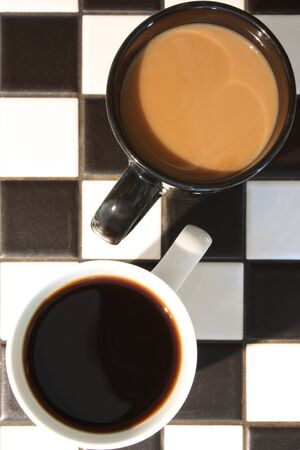 Two cups of coffee, one white  no cream , one black  with cream , on a black and white tile countertop  Possible concept shot for difference or contrast