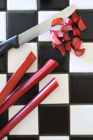 Three stalks of fresh garden rhubarb on a black and white tile counter, being cut with a serrated knife on a retro black and white tile counter