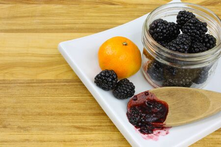 Blackberries in a jar, with a clementine orange and a wooden spoon of blackberry jam on a white plate sitting on a wooden countertop