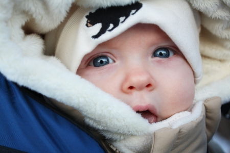 A close up image of a baby in a parka and a tuque Stock Photo