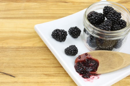 Blackberries in a jam jar, with three more blackerries and a wooden spoon holding blackberry jam, all on a white plate, set on a wooden counter top  Stock Photo