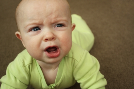 A baby in a light green outfit on a brown carpet, crying and looking angry  Stock Photo
