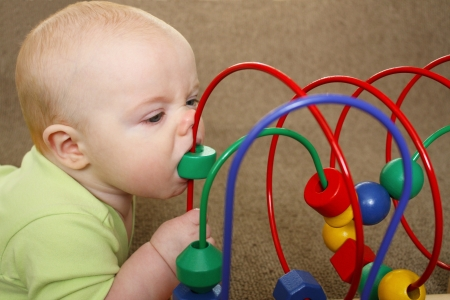 An infant biting a bead on a colorful bead maze toy and making a funny face