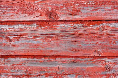 A background image of peeling red paint on old barn boards