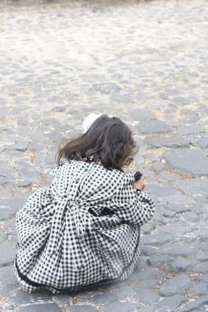 to crouch: A little girl with messy hair in a black and white dress playing on a cobbled street in Guatemala  Stock Photo