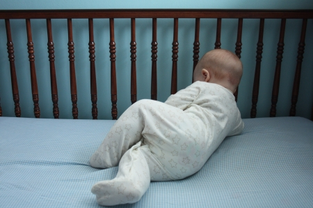 A baby in a white outfit in a wooden crib with blue checked sheets and blue painted walls  Stock Photo - 16991470
