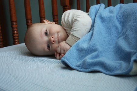 A baby wearing a white outfit playing in a wooden crib with blue checked sheets and a blue blanket in a blue-painted room