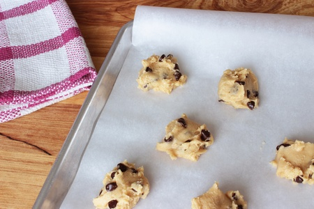 A close-up image of a cookie sheet lined with parchment paper, with chocolate chip cookie dough shaped into cookies, on a wooden counter with a red and white dish towel.