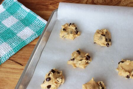 A close-up image of a cookie sheet lined with parchment paper, with chocolate chip cookie dough shaped into cookies, on a wooden counter with a green and white dish towel.