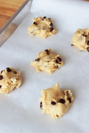 A close-up image of a cookie sheet lined with parchment paper, with chocolate chip cookie dough shaped into cookies, on a wooden counter.