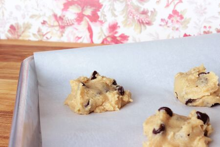 A close-up image of a cookie sheet lined with parchment paper, with chocolate chip cookie dough shaped into cookies, on a wooden counter with a red and white vintage flowered wallpaper background. Stock Photo