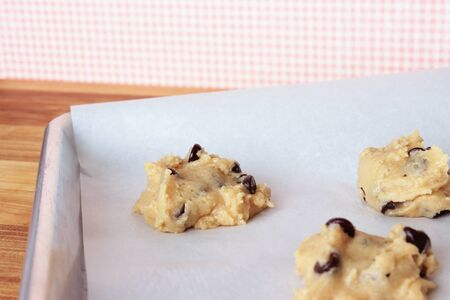 A close-up image of a cookie sheet lined with parchment paper, with chocolate chip cookie dough shaped into cookies, on a wooden counter with a pink and white gingham wallpaper background. Stock Photo
