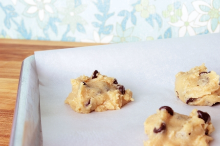 A close-up image of a cookie sheet lined with parchment paper, with chocolate chip cookie dough shaped into cookies, on a wooden counter with a vintage blue, white, and green flowered wallpaper background.