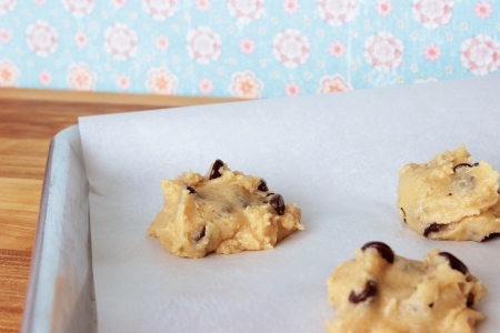A close-up image of a cookie sheet lined with parchment paper, with chocolate chip cookie dough shaped into cookies, on a wooden counter with a vintage blue and pink flowered wallpaper background. Stock Photo