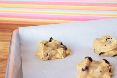 A close-up image of a cookie sheet lined with parchment paper, with chocolate chip cookie dough shaped into cookies, on a wooden counter with a pink and orange striped wallpaper background.