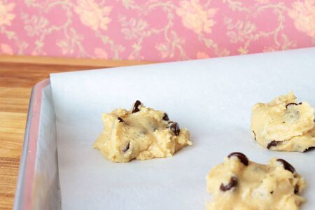 A close-up image of a cookie sheet lined with parchment paper, with chocolate chip cookie dough shaped into cookies, on a wooden counter with a dark pink vintage flowered wallpaper background. Stock Photo