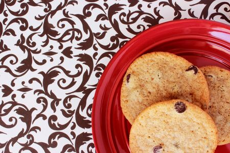 A close-up image of three delicious home made chocolate chip cookies on a red plate, on a retro black and white table cloth.